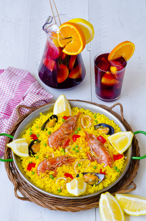 food and wine: Spanish Cuisine. Paella in a pan view from above and fresh sangria in background. Taken in daylight.