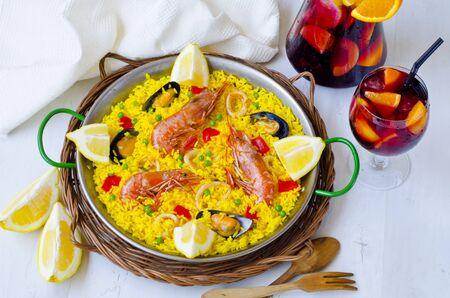 Spaanse Keuken. Paella in een pan weergave van bovenaf en verse sangria in de achtergrond. Genomen in het daglicht. Stockfoto