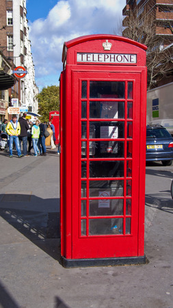 red box: London, United Kingdom - March 31, 2015: A traditional red phone box in Queensway. Incidental people in background.