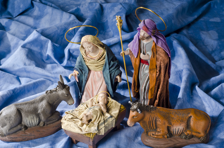 joseph: Christmas Crib. Figures of Baby Jesus, Virgin Mary and St. Joseph. Selective focus. Blue background. Stock Photo