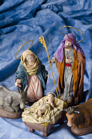 st  joseph: Christmas Crib. Figures of Baby Jesus, Virgin Mary and St. Joseph. Selective focus. Blue background. Stock Photo