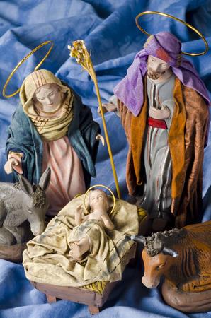cristianismo: Pesebre de Navidad. Las figuras del Niño Jesús, la Virgen María y San José. Enfoque selectivo. Fondo azul.