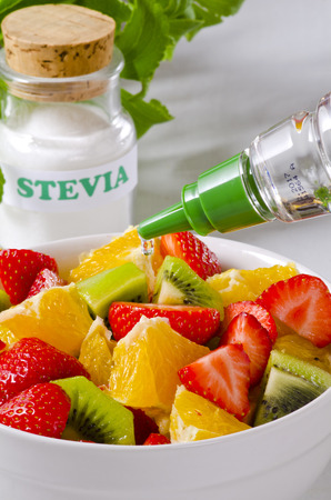 Stevia Drops pouring into fruit salad bowl.  Natural sweetener. Selective Focus. Stock Photo