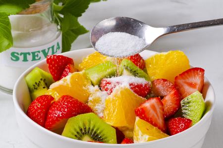 ensalada de frutas: Stevia en polvo que vierte en el tazón de ensalada de frutas. edulcorante natural. Enfoque selectivo.