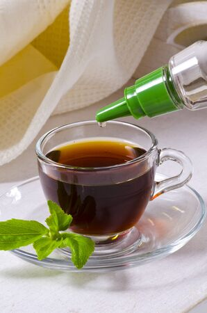 Stevia Drops pouring into a cup of coffee.  Natural sweetener. Selective Focus. Stock Photo