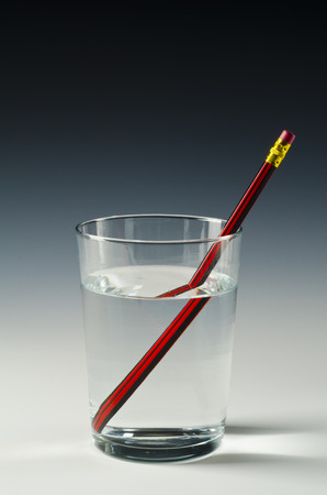 A pencil in a glass of water shows light refraction. Reklamní fotografie