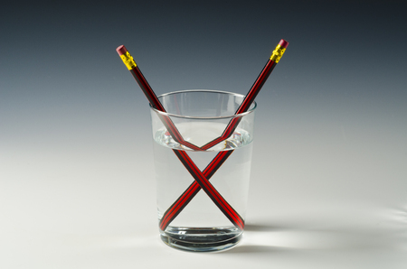 A pencil in a glass of water shows light refraction.