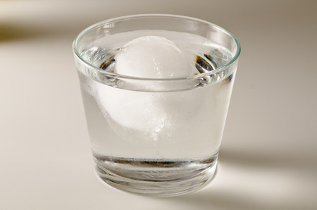 Physics. Ice cube floating in a glass of water. Archimedes principle.