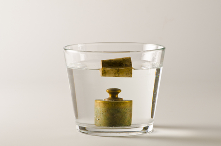 Physics. A cork floats in water and  a antique weight sinks. Archimedes Principle.