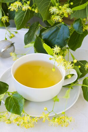 Alternative Medicine. Herbal Therapy. Lime blossom tea in cup. White background.
