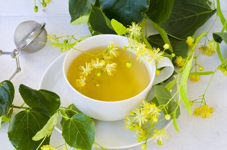 Alternative Medicine. Herbal Therapy. Lime blossom tea in a cup. White background. Stok Fotoğraf