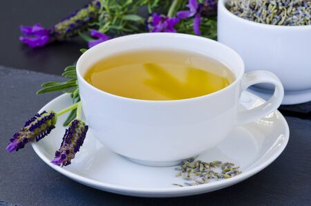 Alternative Medicine. Herbal Therapy. Lavender tea in a cup. Black background. Stok Fotoğraf - 132001078