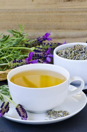 Alternative Medicine. Herbal Therapy. Lavender tea in a cup. Wooden background. Copyspace.
