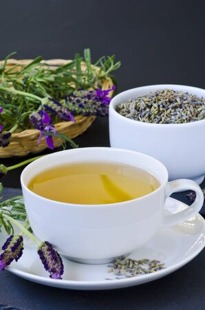 Alternative Medicine. Herbal Therapy. Lavender tea in a cup. Black background. Stok Fotoğraf