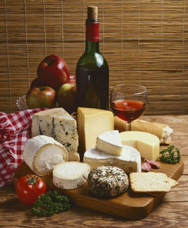 Assorted cheese and red wine on a wooden board.