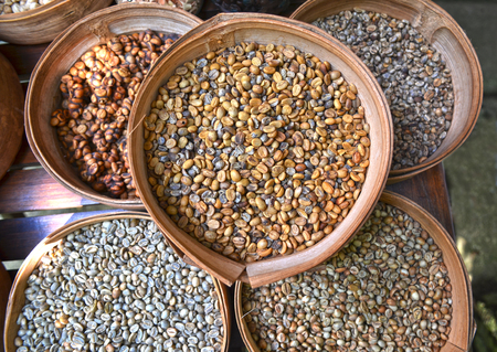 coffee beans: Various unroasted coffee beans on different bamboo baskets Stock Photo