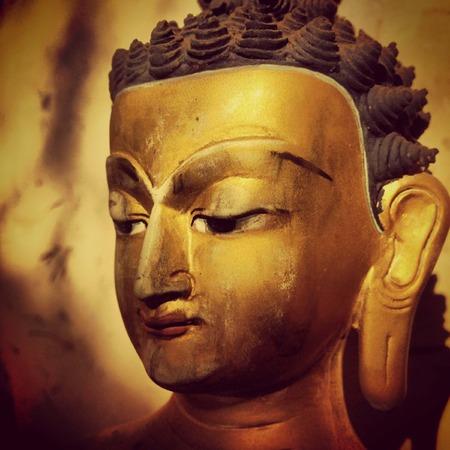 mediate: head shot of gold buddha in soft warm morning light Stock Photo