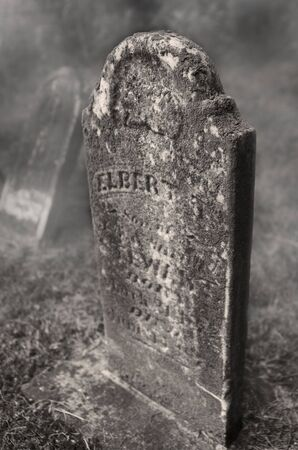An old gravestone, too worn to read, on a misty day.