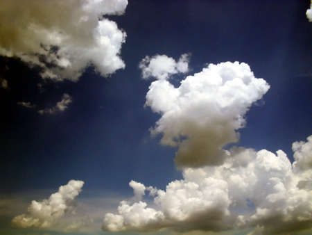 puffy: Sun Rays through the clouds,clouds in manny shapes Stock Photo