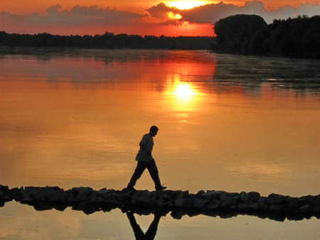 Walking Through the Fire and Water,man on the river at sunset Stock Photo - 2376640