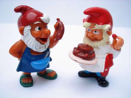 gnomos: Dos gnomos sonriendo con los alimentos en las manos  Foto de archivo