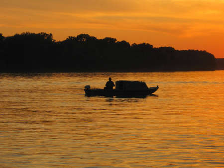 Fisherman in the boat on the river,sunset photo