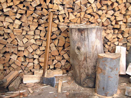 pile of logs: axe blade resting in a piece of firewood Stock Photo