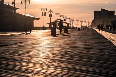 Mensen die op de promenade op Coney Island bij zonsondergang lopen