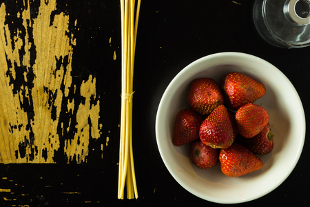 A glass jar, incense sticks  and a bowl of strawberries are arranged on a scratchy wooden surface Stock Photo