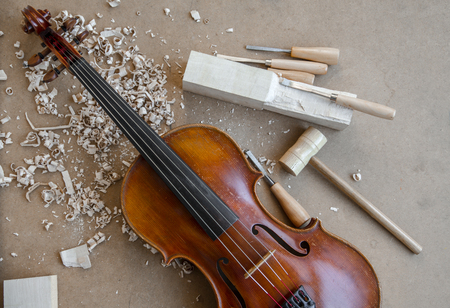 violin making: Red brown violin on luthiers desk. Carving tools, sawdust and wooden hammer. Stock Photo