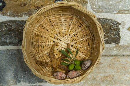 spiffy: Fancy wicker basket on stone wall. Starfish, leaves and seashells inside. Stock Photo