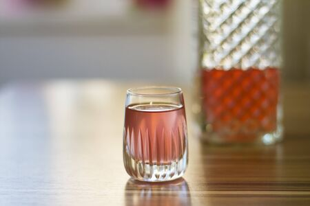 Pink colored liqueur in a crystal shot glass on wooden table. Bootle at the background. Soft and selective focus. Stock Photo