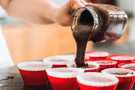 Housewife pours chocolate dough into baking molds for cupcakes. Close up. Banque d'images