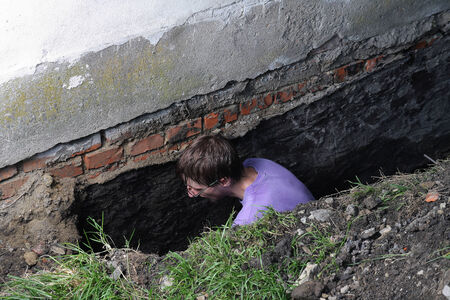 Young man preparing hole in ground for Installation of new studded film as insulation against ground moisture photo