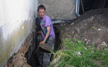 dampness: Young man preparing hole in ground for Installation of new studded film as insulation against ground moisture Stock Photo