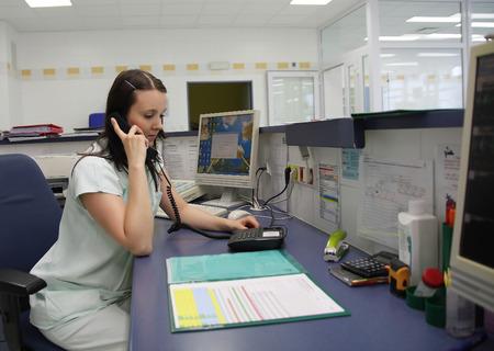 enfermeras: Enfermera llamada en el tel�fono en la UCI Foto de archivo