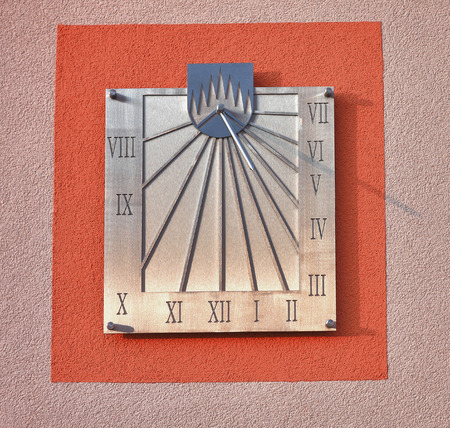 Sundial on facade of  house in sunny day photo