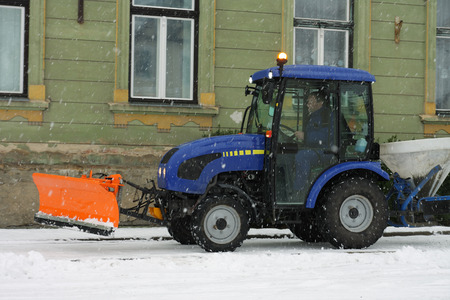 A tractor on a road during  snow storm Stock Photo