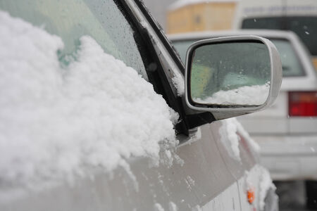 driving conditions: Snow covered car during a snowstorm in street
