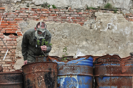explores: Man with gas mask and green military clothes  explores  small plant  after chemical disaster. Stock Photo
