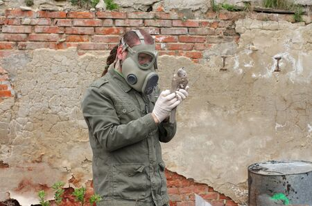 explores: Man with gas mask and green military  clothes  explores  dead bird after chemical disaster.