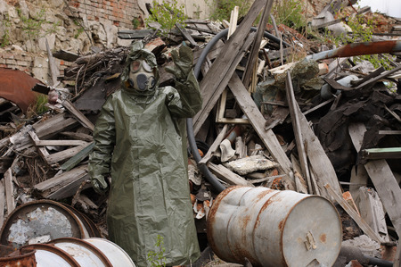 explores: Man with gas mask and green military clothes  explores  after chemical disaster. Stock Photo