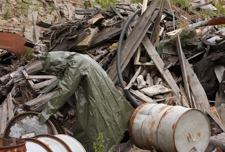 explores: Man with gas mask and green military clothes  explores barrels  after chemical disaster.
