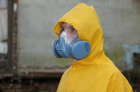 explores: Man with protective  mask and protective  clothes  explores danger area.