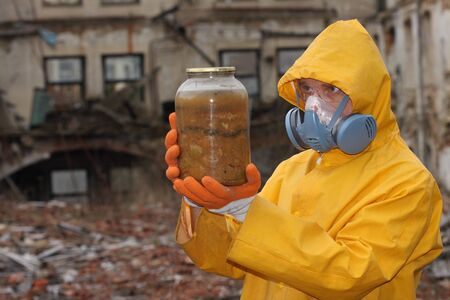 explores: Man with protective  mask and protective  clothes  explores danger jar.