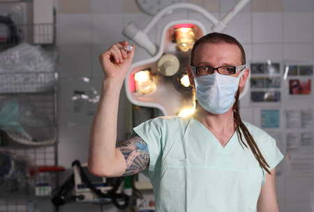 Portrait of  male nurse ICU  with tattoo and dreadlocks on emergency room with syringe in hand photo