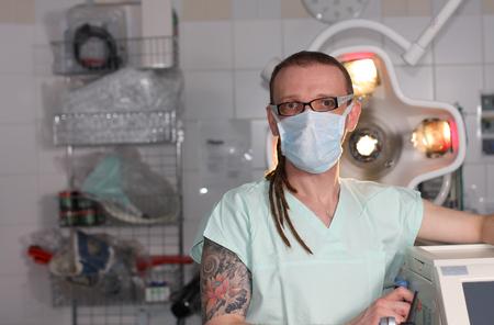 medical ventilator: Portrait of  male nurse ICU  with tattoo and dreadlocks on emergency room with ventilator