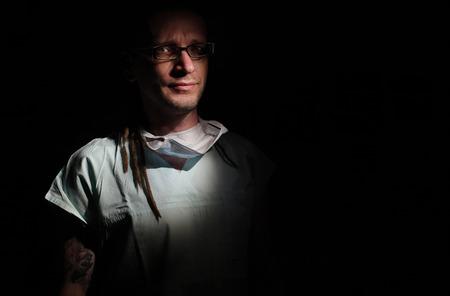 icu: Portrait of  male nurse ICU  with tattoo and dreadlocks on black background