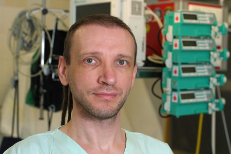 icu: Portrait of  male nurse ICU  on emergency room.Perfusors and monitor are in background. Stock Photo