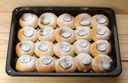 baking tray: cottage cheese cakes  with jam on baking tray on  wooden table Stock Photo